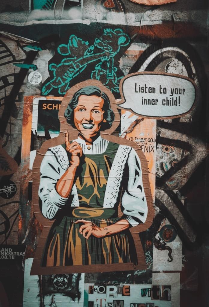 "The image shows wall art. A woman is dressed in 1950's style. A speech bubble next to her says, "" Listen to your inner child"" There are cartoons and graffiti on the wall too"